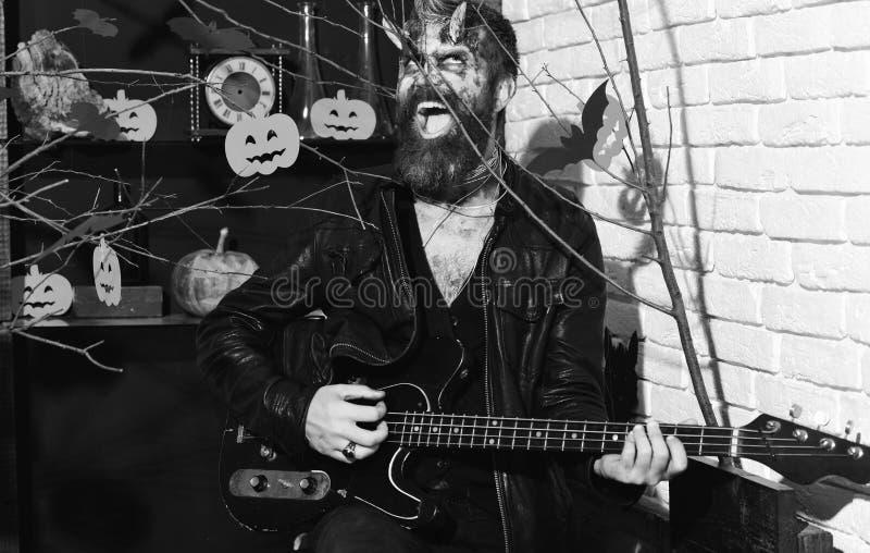 Le démon avec des klaxons et le sourire fou tient la guitare électrique noire photo libre de droits