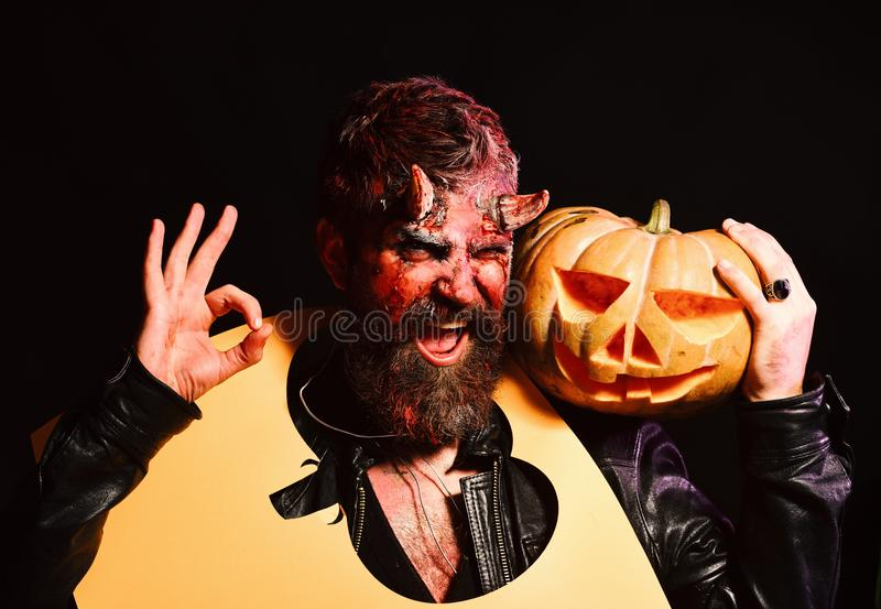 Le démon avec le sourire tient la lanterne du cric o et montre le signe correct Concept de partie de Halloween Homme portant la c photo libre de droits