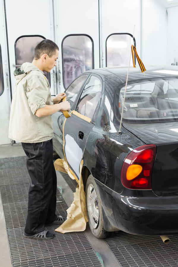 Le dépanneur préparent la voiture pour peindre sur l'atelier de carrosserie image libre de droits