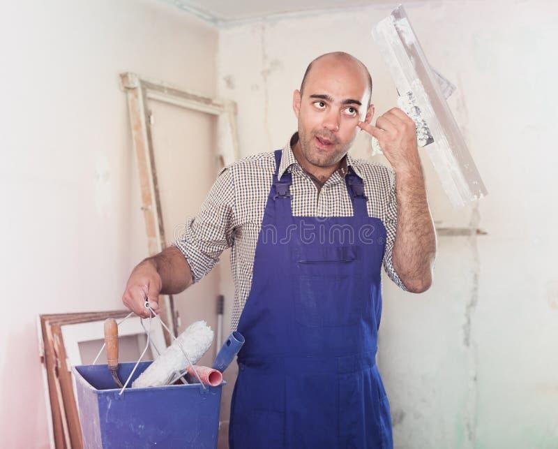 Le dépanneur se tient avec le couteau de seau et de mastic image libre de droits