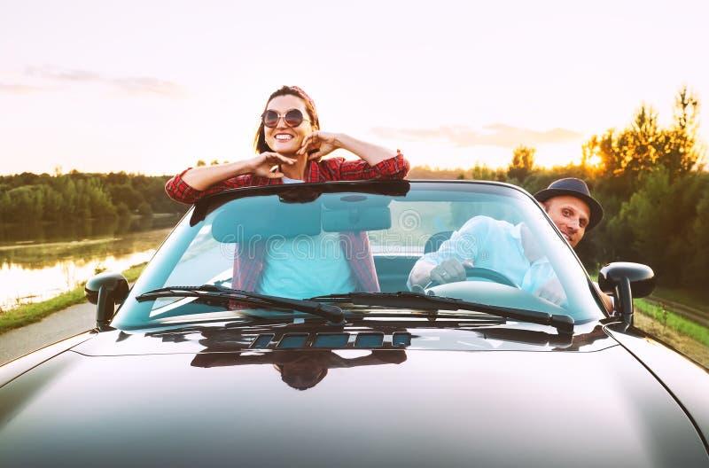 Le déplacement par les couples automobiles dans l'amour vont en voiture de cabriolet dans le coucher du soleil photos stock
