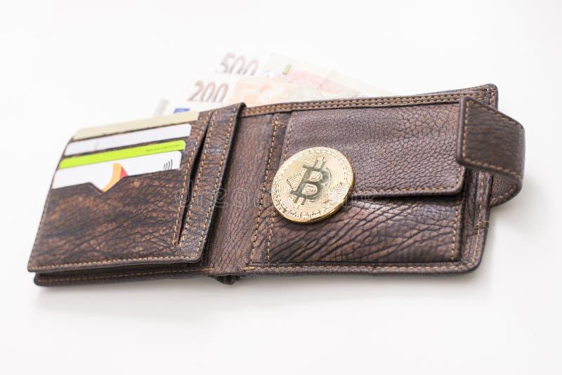 Le détail d'un portefeuille en cuir ouvert avec un grand Bitcoin d'or, des notes de Fiat et des cartes de crédit et bleu a allumé photos libres de droits