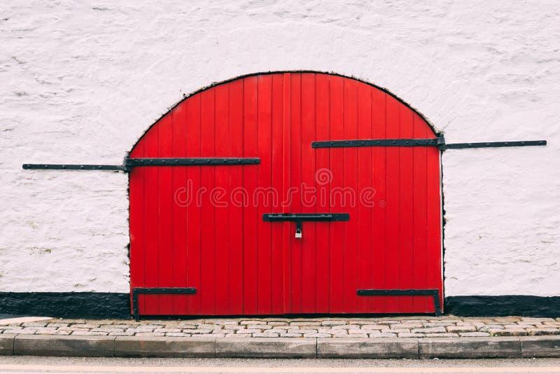 Le détail d'une porte rouge de vieille grange avec le métal noir s'articule contre un mur blanc photos libres de droits
