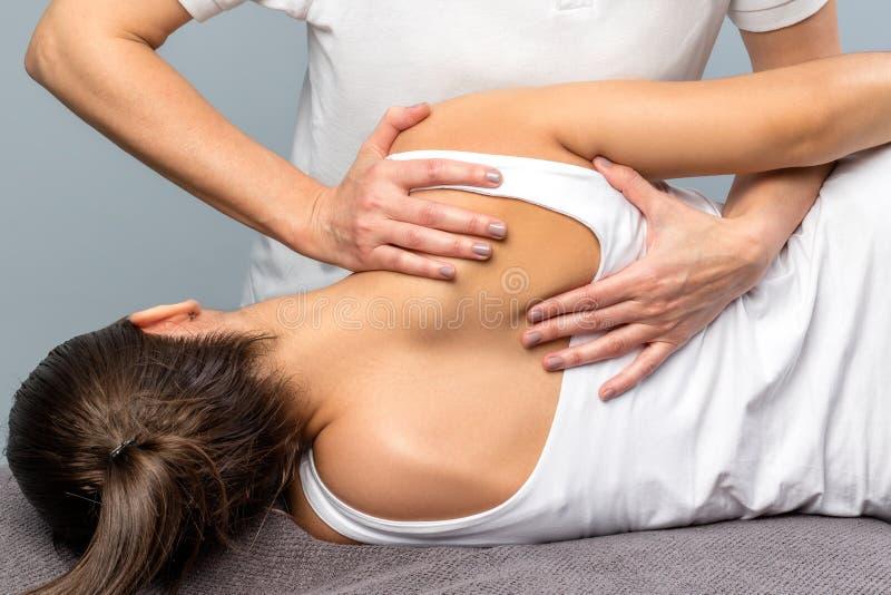 Le détail de l'omoplate de manipulation de thérapeute féminin patien dessus photos libres de droits