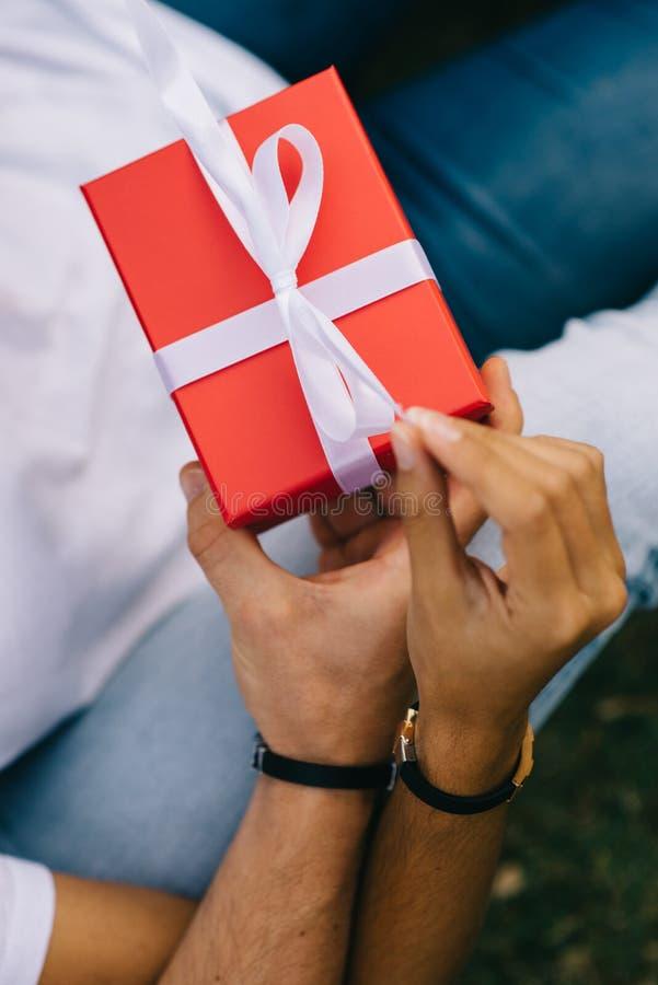 Le détail des couples remet ouvrir un présent dans une boîte rouge photo libre de droits