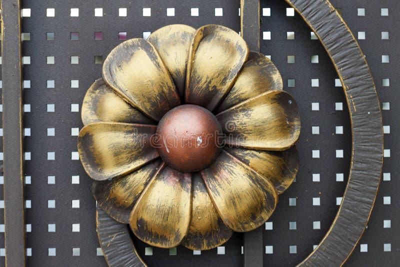 Le détail en gros plan du beau vintage a forgé fleur jaune en métal la grande et rouge décorant la barrière, la porte ou la porte image libre de droits