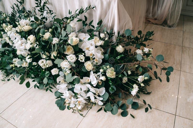 Le d?cor de mariage, accessoires, orchid?es, roses, l'eucalyptus, un bouquet dans un restaurant, pr?side l'arrangement de table photos stock