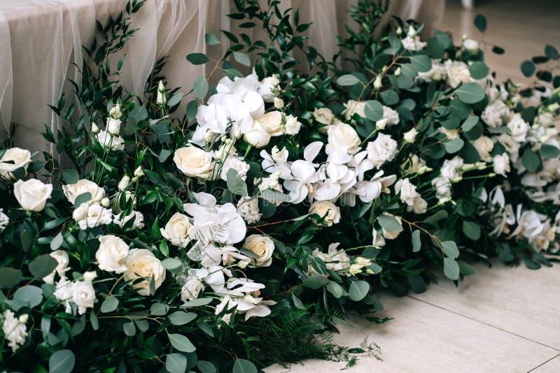Le d?cor de mariage, accessoires, orchid?es, roses, l'eucalyptus, un bouquet dans un restaurant, pr?side l'arrangement de table images libres de droits