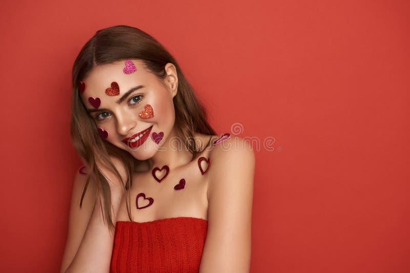 Le damen dekoreras med hj?rta-formade klisterm?rkear p? f?rgbakgrund arkivfoto