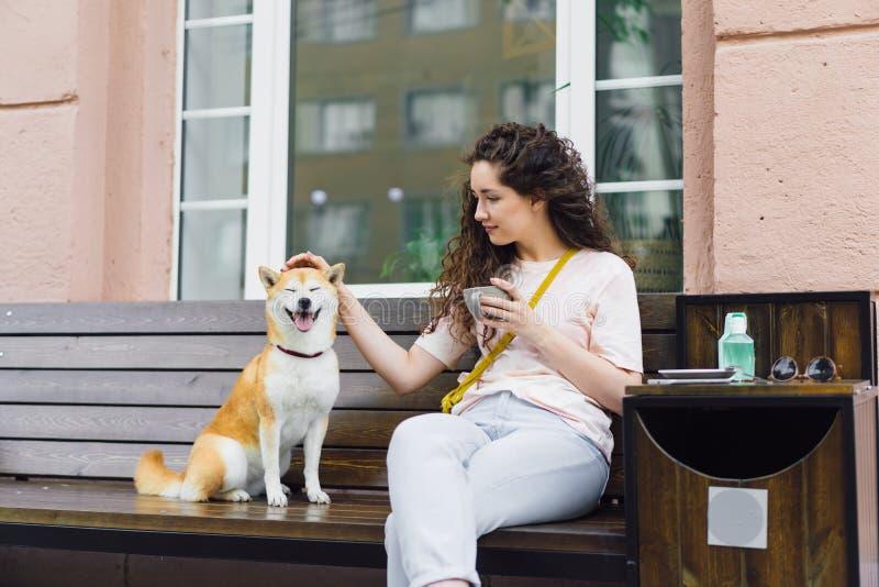 Le damen som slår den härliga hunden och att rymma koppen kaffe i gatakafé royaltyfri foto