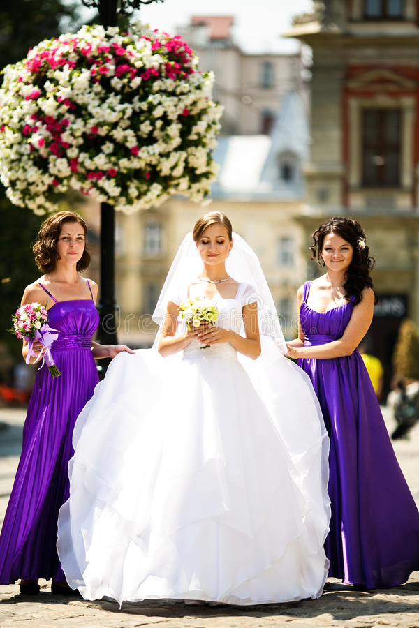 Le damigelle d'onore aiutano la sposa a mettere sopra gli orecchini e la collana fotografia stock