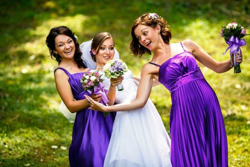 Le damigelle d'onore aiutano la sposa a mettere sopra gli orecchini e la collana immagine stock