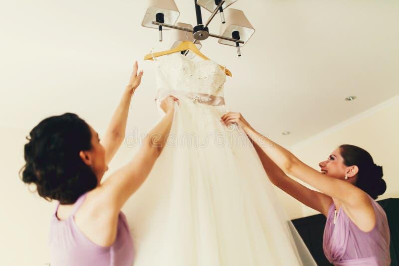 Le damigelle d'onore provano a mettere fuori un vestito da un candeliere fotografie stock libere da diritti
