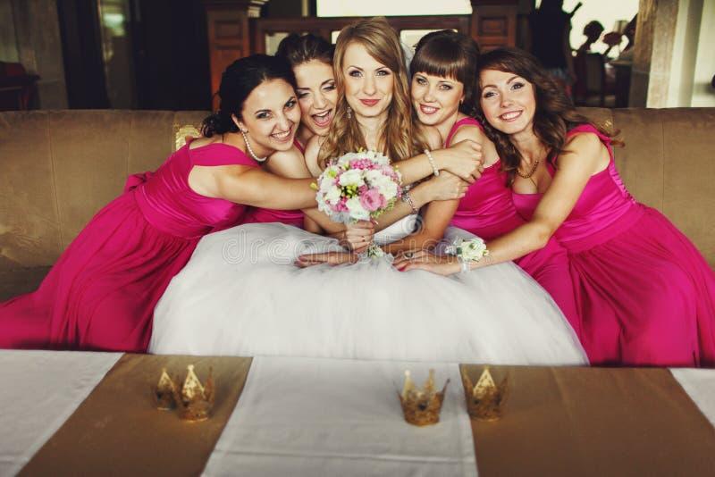 Le damigelle d'onore in vestiti rosa pendono ad una sposa graziosa che si siede sul Th fotografie stock libere da diritti