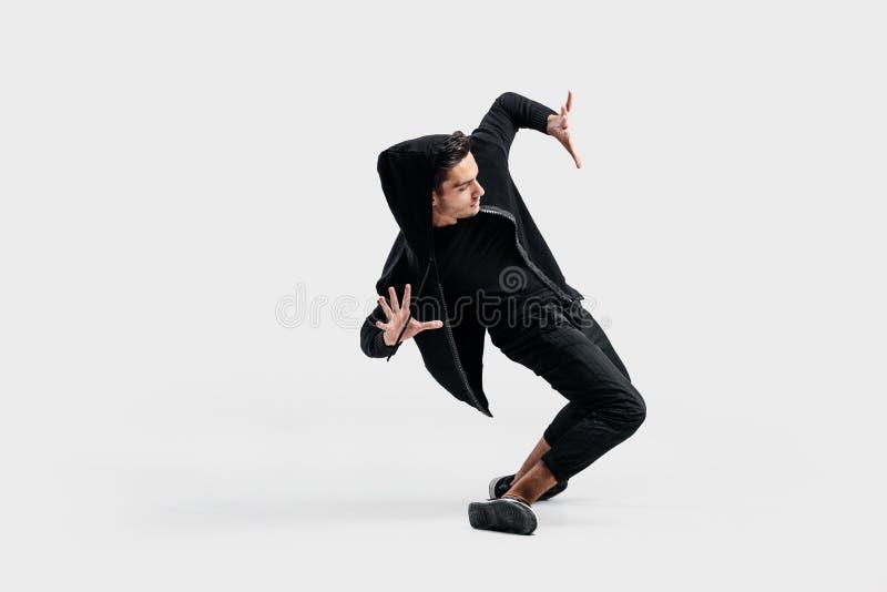 le danseur élégant aux cheveux foncés habillé dans les vêtements noirs fait les mouvements stylisés de la danse de rue photo stock