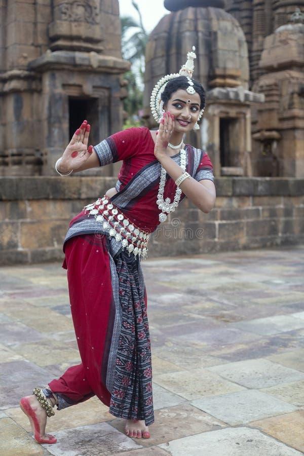 Le danseur classique féminin d'Odissi utilise le costume traditionnel avec le mudra de main au temple de Mukteshvara, Odisha, Ind photographie stock