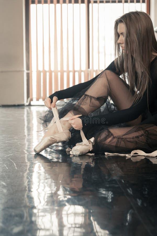 Le danseur classique féminin met des pointes dessus image stock