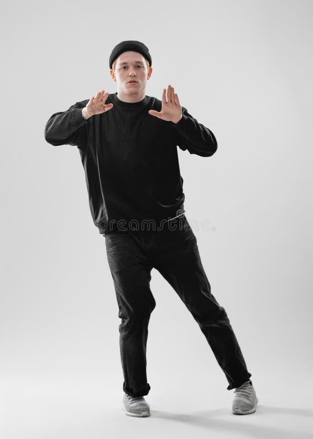 Le danseur de type habillé dans les jeans noirs, le pull molletonné, le chapeau et des espadrilles grises danse dans le studio su images libres de droits