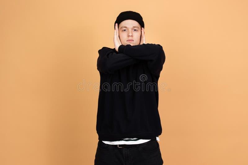 Le danseur de type habillé dans les jeans, le pull molletonné et le chapeau noirs tient ses mains sur sa tête sur le fond beige d photo stock