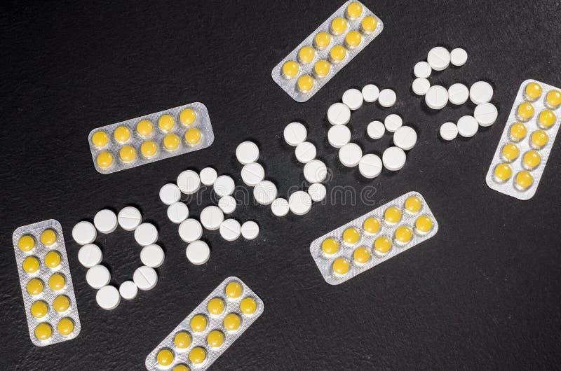 Le ` de drogues de ` de mot est présenté des pilules sur un fond foncé avec des paquets des pilules image libre de droits