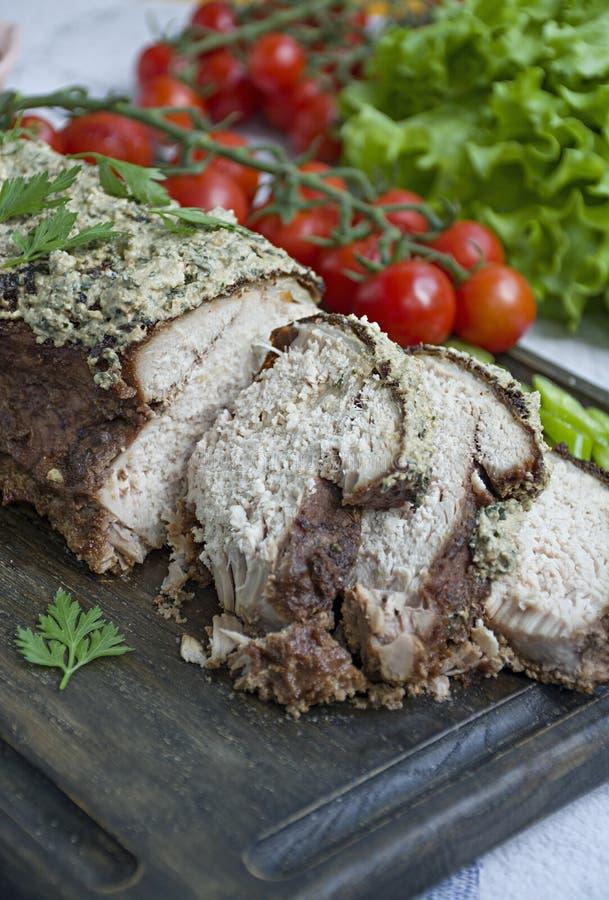 Le de porc cuit au four côtelette dans une noix et une sauce en bon état sur une planche à découper avec les herbes et les légume image libre de droits