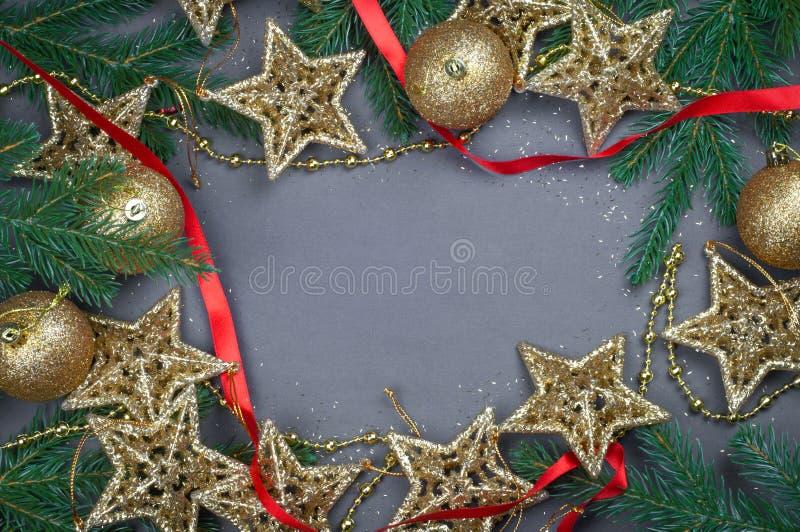 Le decorazioni rosse e dorate di Natale gioca le palle ed il fondo delle stelle con una ghirlanda delle luci immagine stock