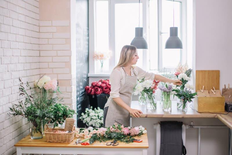 Le den älskvärda blomsterhandlaren för ung kvinna som ordnar växter i blomsterhandel royaltyfri bild