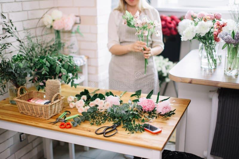 Le den älskvärda blomsterhandlaren för ung kvinna som ordnar växter i blomsterhandel arkivbild