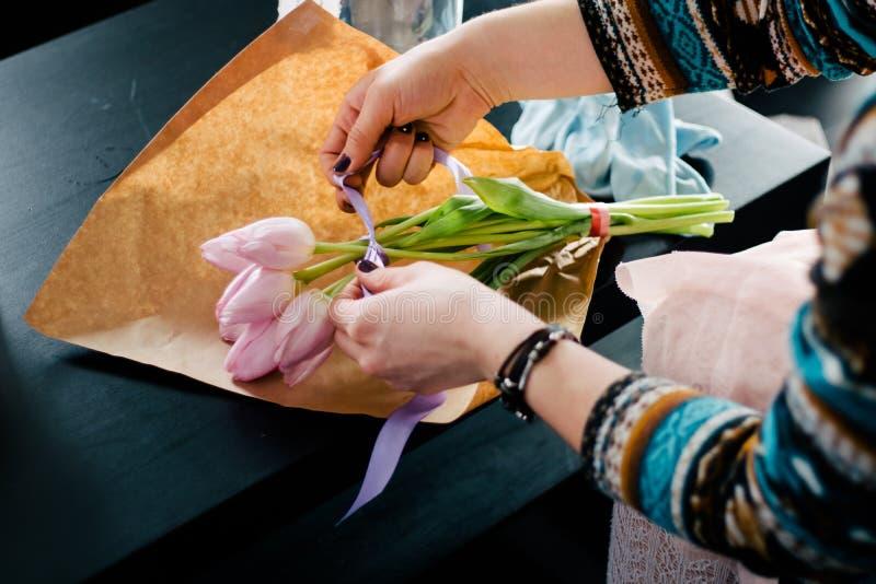 Le den älskvärda blomsterhandlaren för ung kvinna som ordnar växter i den sh blomman arkivfoto