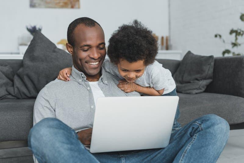 le den afrikansk amerikanfadern och sonen som sitter på golv och att använda bärbara datorn royaltyfri foto