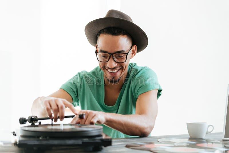 Le den afrikanska mannen i t-skjorta genom att använda skivspelaren arkivfoton