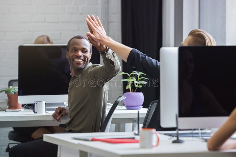 Le den afrikanska mannen som ger höga fem till en manlig kollega royaltyfria bilder