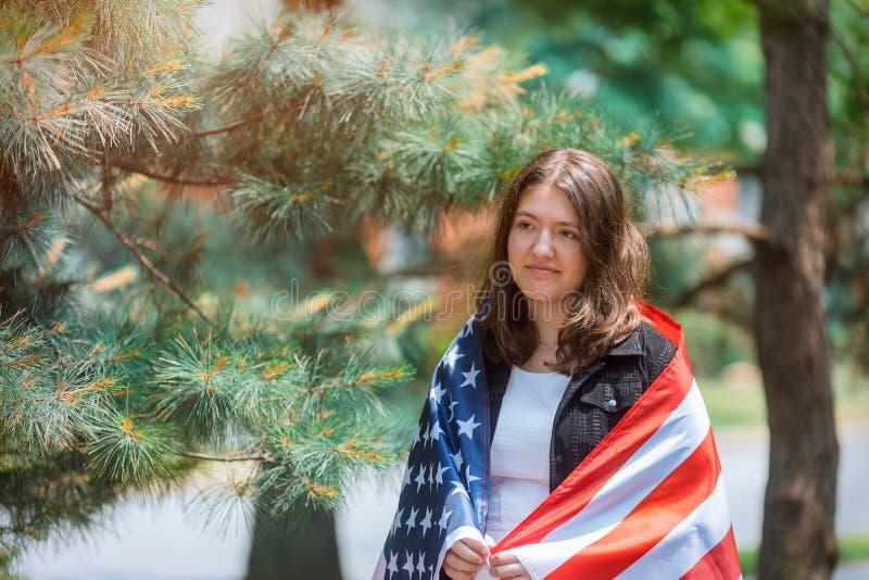 Le den amerikanska flickan som rymmer USA flaggan och att se kamerasj?lvst?ndighetsdagen royaltyfri bild