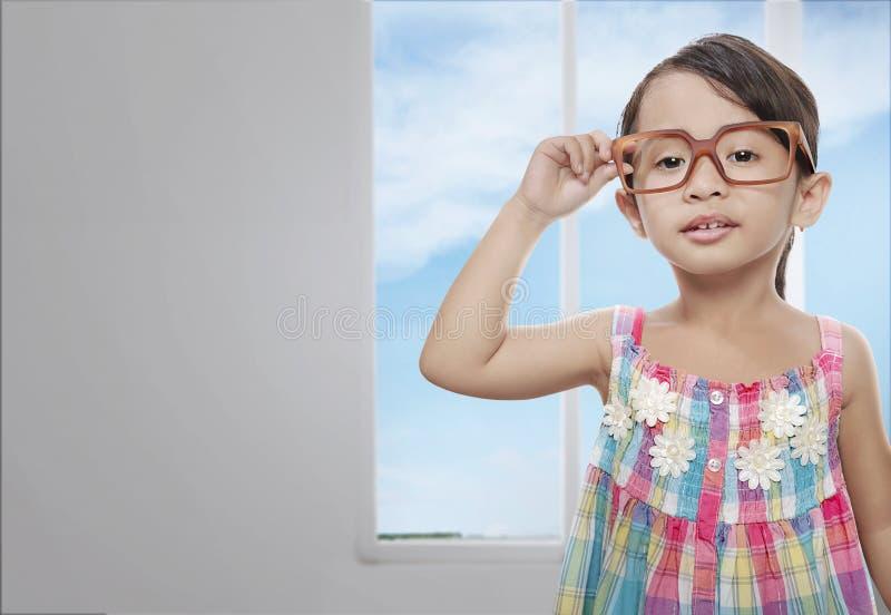 Le den asiatiska flickan med att stå för glasögon royaltyfria foton