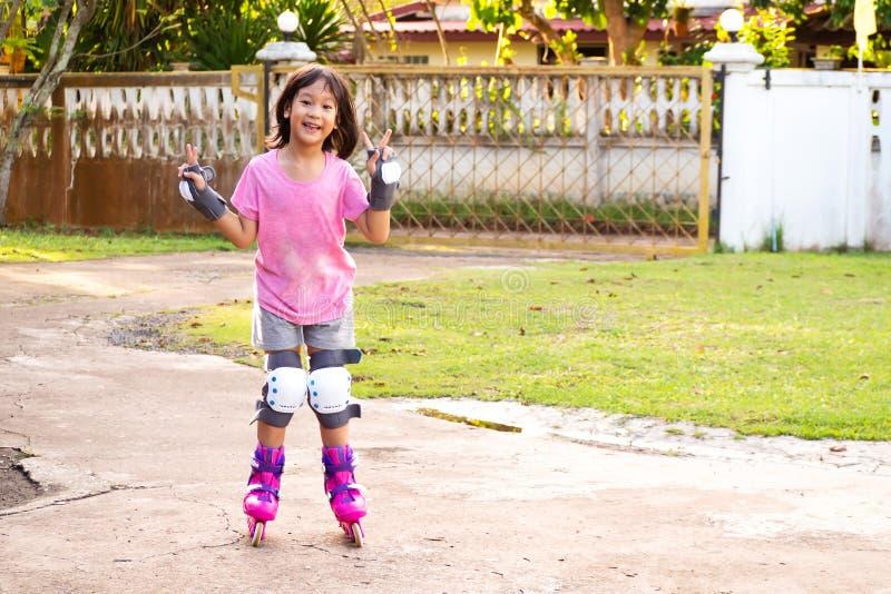 Le den asiatiska flickan som spelar rollerblading hemma Fritidsport royaltyfria bilder