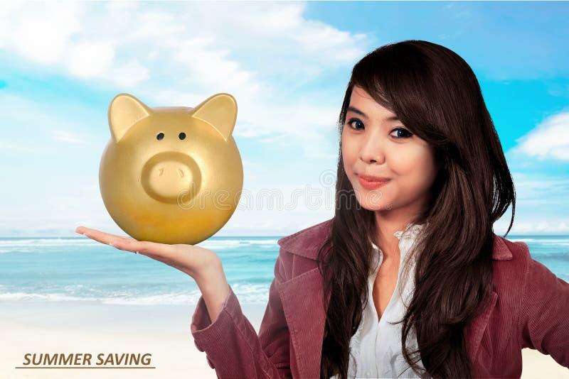 Le den asiatiska hållande spargrisen för affärskvinna arkivfoton