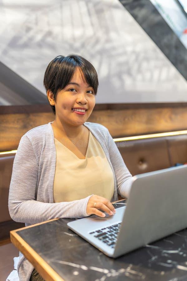 Le den asiatiska kvinnan för kort hår som arbetar med bärbara datorn fotografering för bildbyråer
