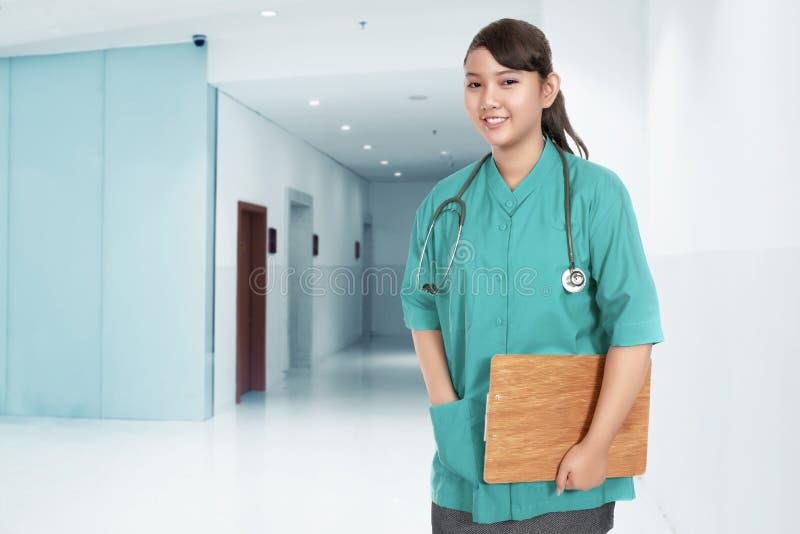 Le den asiatiska kvinnan för medicinsk doktor med stetoskopet i hennes hals arkivfoto