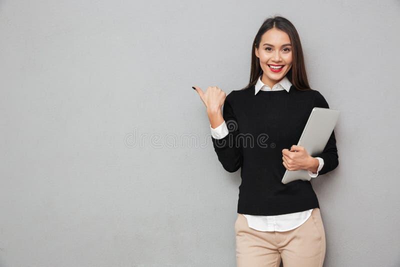 Le den asiatiska kvinnan i affär beklär den hållande bärbar datordatoren royaltyfri fotografi