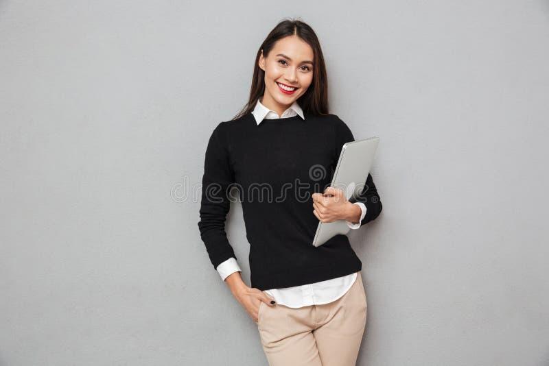 Le den asiatiska kvinnan i affär beklär den hållande bärbar datordatoren arkivfoto