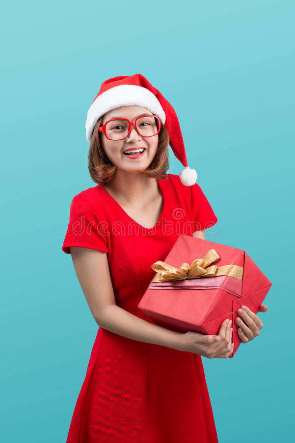 Le den asiatiska kvinnan i röd gåva för santa hattinnehav boxas royaltyfri bild