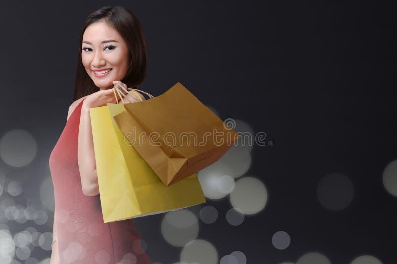 Le den asiatiska kvinnan med påseshopping i svarta fredag semestra arkivfoto