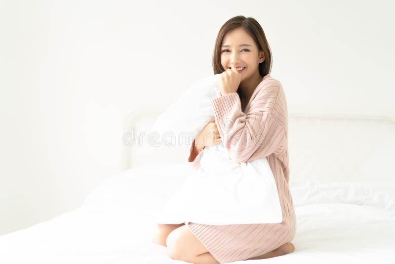 Le den asiatiska kvinnan som bär stucken rosa förkylning för tröja som sitter i säng som kramar en kudde och att se kameran Begre arkivfoton