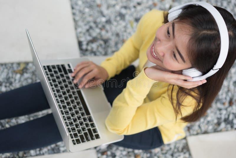 Le den asiatiska unga flickan med lyssnande musik f?r b?rbar dator vid headphonen arkivfoton