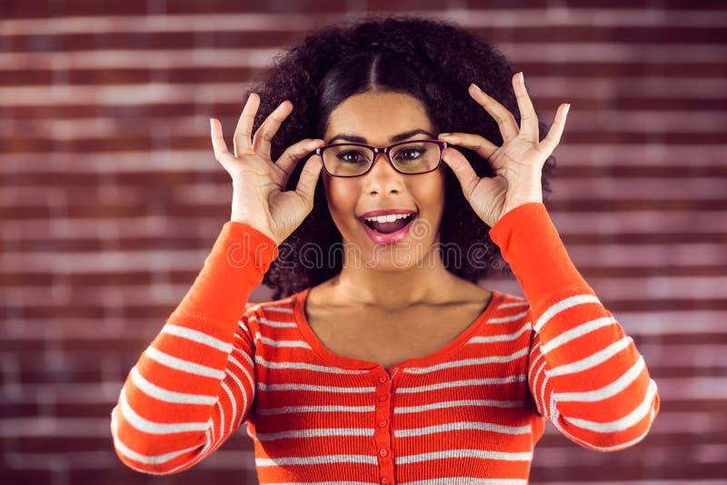 Le den attraktiva kvinnan som poserar med hipsterexponeringsglas royaltyfri foto