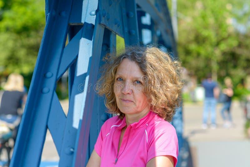 Le den attraktiva kvinnan som ser till och med en bro royaltyfri fotografi