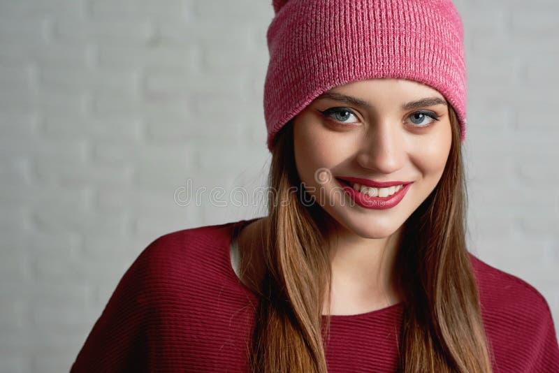Le den attraktiva kvinnlign i röd hatt och tröjan som bär det härliga yrkesmässiga sminket som poserar till kameran royaltyfri foto