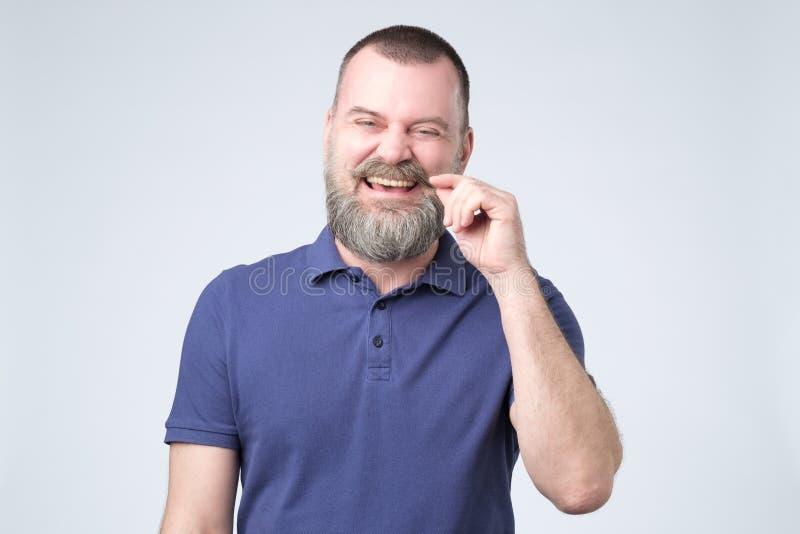 Le den attraktiva mogna mannen med skägget i den blåa t-skjortan som ser direkt på kameran royaltyfri bild