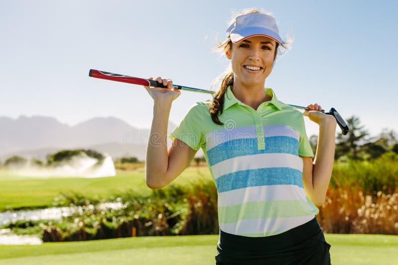 Le den bärande golfklubben för ung kvinnlig golfare royaltyfri bild