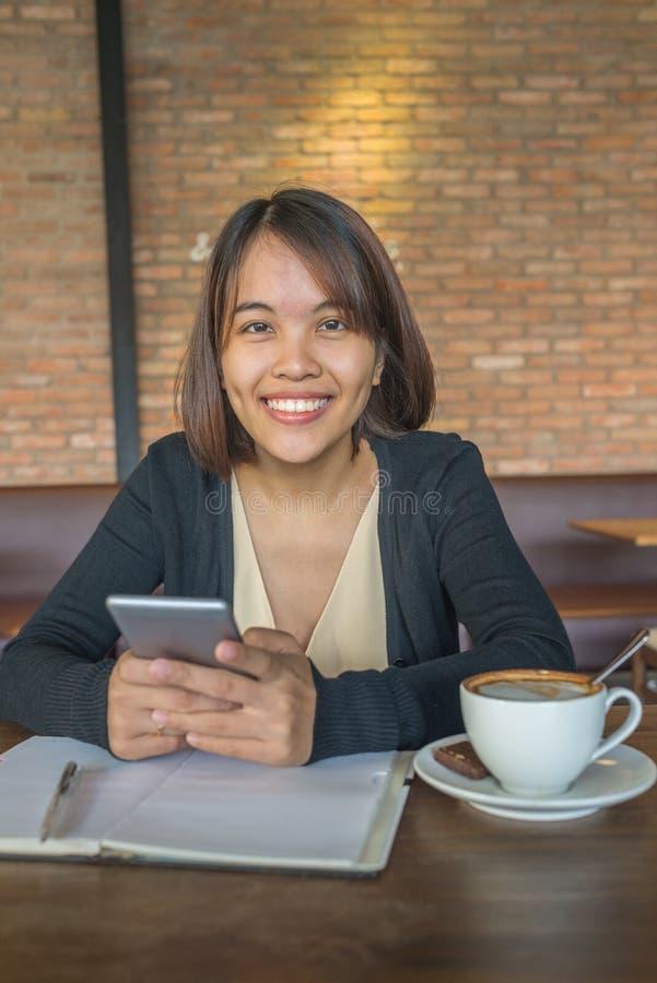 Le den bärande smartphonen för asiatisk kontorsdam royaltyfria bilder
